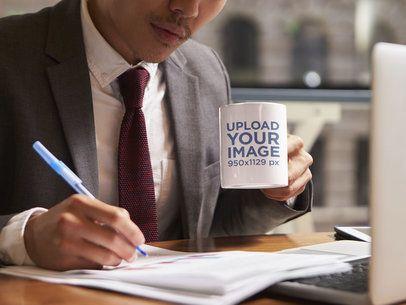 Mockup of a Man Holding an 11 oz Coffee Mug While Working 43578-r-el2