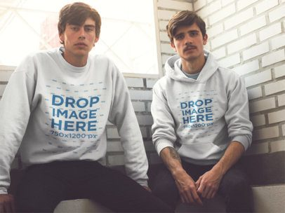 Two Serious Friends Wearing Matching Designs on a Pullover Hoodie and a Crewneck SweatshirtWhile Sitting Against a White Bricks Wall Mockup a13408