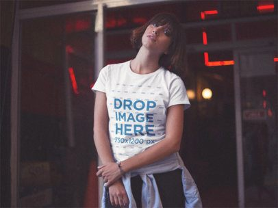 Young Woman Wearing a Round Neck Tee While Near a Closed Store with Red Lights Mockup a13568