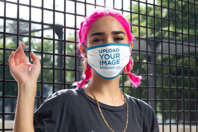 Face Mask Mockup Featuring a Young Woman With Pink Hair Posing by a Fence m402