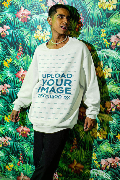 Mockup of a Man with an Oversize Sweatshirt Leaning on a Floral Wall m572