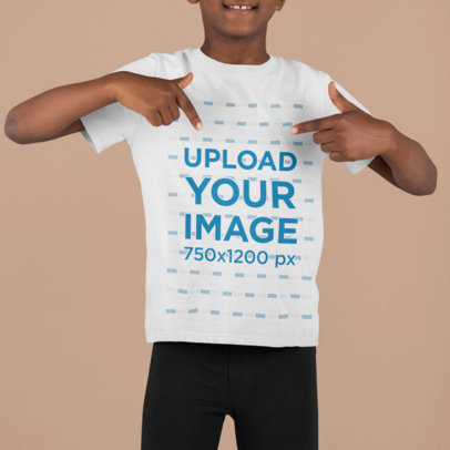 Mockup of a Boy at a Studio Pointing at His Customizable T-Shirt m855