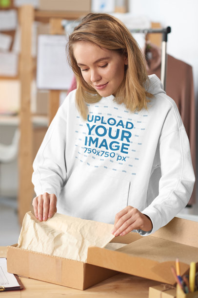 Hoodie Mockup Featuring a Young Woman Packing Some Items for Shipping 45669-r-el2