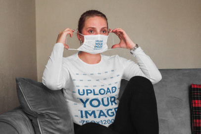 Mockup of a Woman on Her Couch Wearing a Face Mask and a Long Sleeve Tee 46223-r-el2