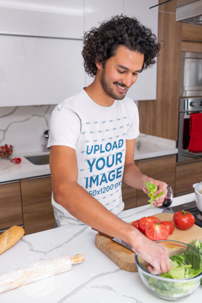 T-Shirt Mockup Featuring a Curly-Haired Man Cooking at Home m1050