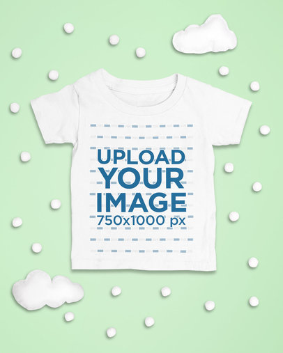 Mockup of a Baby's T-Shirt Laid Flat with Snowy Clouds as an Ornament m1126