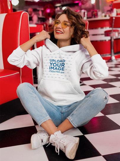 Hoodie Mockup of a Woman Sitting on the Floor of a Retro Diner m2668-r-el2