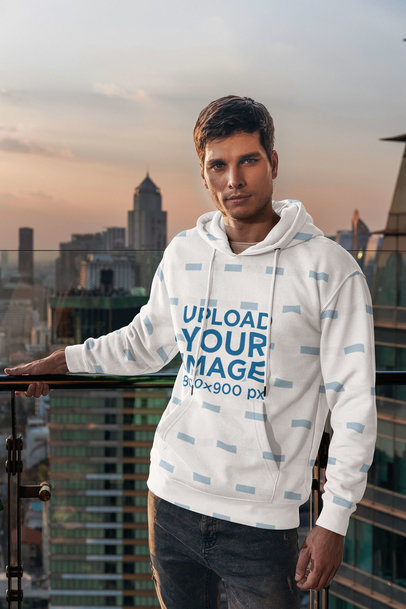 Mockup of a Man Posing with a Sublimated Hoodie in Front of a Skyline 5127-el1