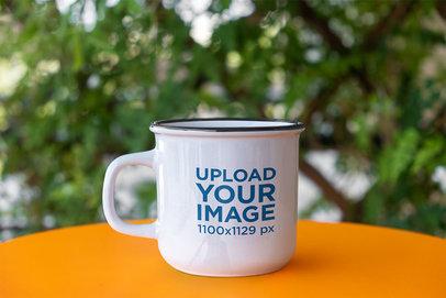 Mockup of a 12 oz Enamel Coffee Mug Placed in an Outdoor Setting m2957-r-el2