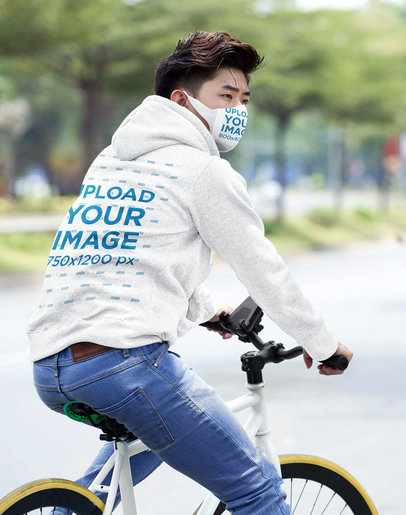Back-View Hoodie Mockup of a Man on a Bike Wearing a Face Mask 36162-r-el2