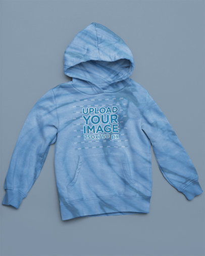Mockup of a Tie-Dye Hoodie Lying on a Flat-Colored Surface m4122
