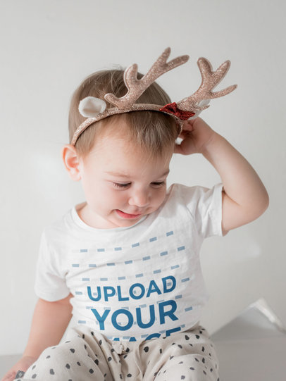 Mockup of a Baby Wearing a Customizable T-Shirt and Reindeer Antlers m2196-r-el2