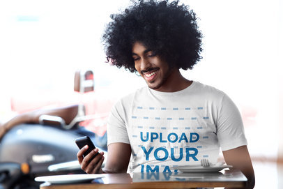 T-Shirt Mockup of a Happy Man With Curly Hair Checking His Phone at a Restaurant 39861-r-el2