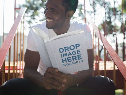 Young Black Man Holding a Paperback Book Mockup  a12035