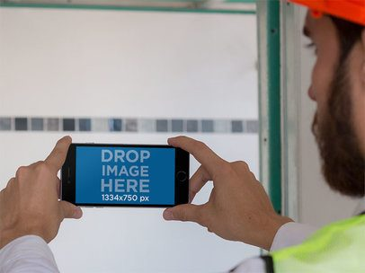 iPhone Mockup of a Construction Man Taking a Picture in Landscape Mode 12422