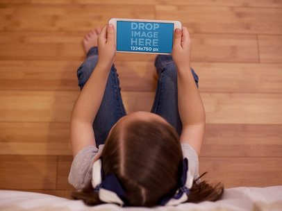 Young Girl Sitting in her Room and Using an iPhone 7 in Landscape Position Mockup a12998