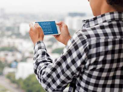 Mockup of an iPhone in Landscape Position Featuring a Man in an Urban Background 13040s