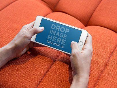 iPhone Mockup in Landscape Position against an Orange Sofa 13106s