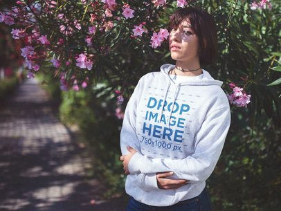 Lovely Girl with Short Hair Wearing a Hoodie Mockup Near a Garden Alley a12680